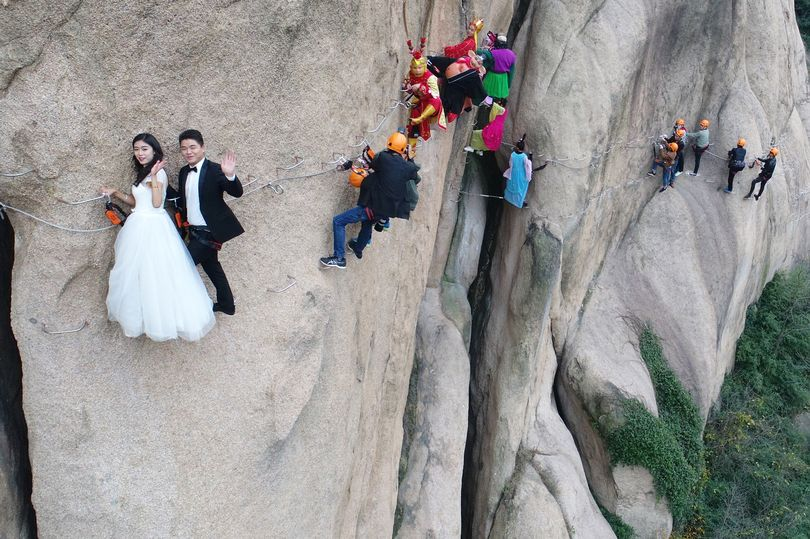 PROD Newlywed Couple Poses For Wedding Photos On Cliff Face In Zhumadian