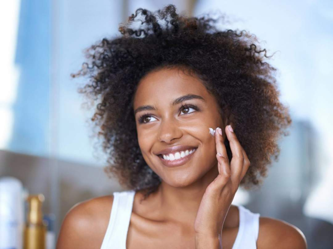 Dark Skinned Woman Applying Moisturiser. Photo Nivea E1563707100869