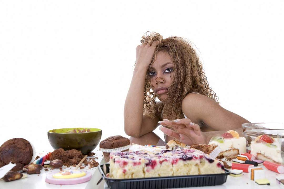 A Woman Sitting In Front Of Sugary Foods Photo Nutrition Advance