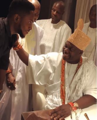 Miracle prostrating partially to greet the Ooni of Ife