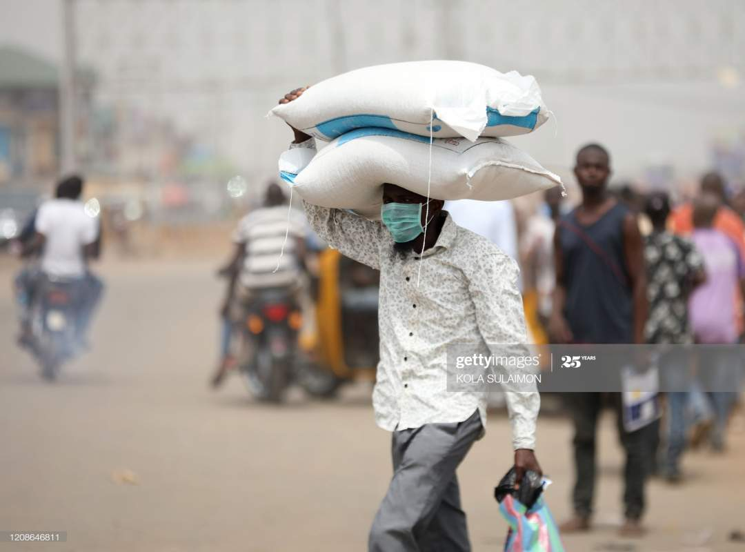 Man Carries Bags Of Rice On His Head At A Border Between Abuja And Picture Id1208646811?s=28
